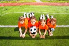 Усмехаясь дети кладут на траву с золотым кубком Стоковые Изображения RF