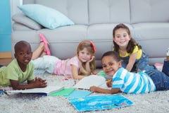 Усмехаясь дети рисуя изображения на бумаге Стоковые Изображения