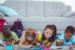 Усмехаясь дети рисуя изображения на бумаге Стоковая Фотография RF