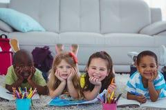 Усмехаясь дети рисуя изображения на бумаге Стоковые Изображения RF