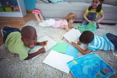 Усмехаясь дети рисуя изображения на бумаге Стоковое Изображение