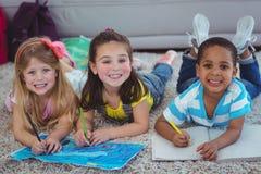 Усмехаясь дети рисуя изображения на бумаге Стоковые Фотографии RF