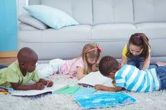 Усмехаясь дети рисуя изображения на бумаге Стоковое Изображение RF