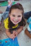 Усмехаясь дети рисуя изображения на бумаге Стоковое фото RF