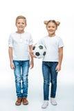Усмехаясь дети стоя с футбольным мячом Стоковая Фотография RF