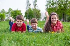 3 усмехаясь дет лежа совместно на зеленом луге Стоковые Изображения RF
