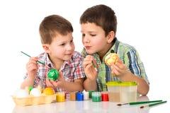 2 усмехаясь дет крася пасхальные яйца совместно на таблице Стоковое Фото