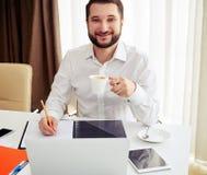 Усмехаясь деятельность человека и выпивает кофе в белом офисе Стоковая Фотография RF