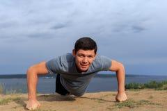 Усмехаясь делать молодого человека нажим-поднимает outdoors стоковое изображение