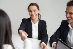 Усмехаясь женская коммерсантка handshaking hr на групповой встрече или Стоковые Фото