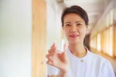 Усмехаясь женская медсестра держа чашку пилюльки в ее руке для пациентов Профессионал, специалист, медсестра, доктор в белой равн стоковые изображения rf