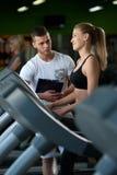 Усмехаясь женская работа с личным тренером в спортзале Стоковые Изображения RF
