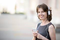 Усмехаясь женская слушая музыка онлайн Стоковая Фотография RF