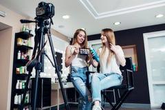 Усмехаясь женские блоггеры красоты рассматривая продукты состава для их блога записывая видео на камере в салоне стоковая фотография