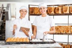 Усмехаясь женские коллеги с таблеткой цифров в хлебопекарне Стоковая Фотография