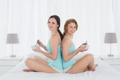 Усмехаясь женские друзья при салатницы сидя спина к спине на кровати Стоковая Фотография RF