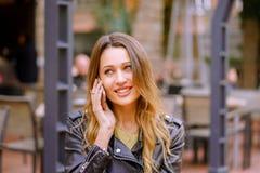 Усмехаясь женский говорить на смартфоне в кафе outdoors стоковые фото