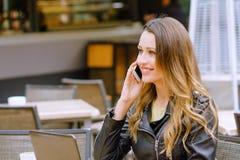 Усмехаясь женский говорить на смартфоне в кафе outdoors стоковая фотография