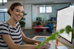 Усмехаясь женский график-дизайнер работая на компьютере Стоковая Фотография RF