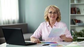 Усмехаясь женский дизайнер смотря камеру, держа образец цвета в руках, работа стоковая фотография rf
