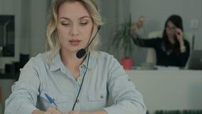 Усмехаясь женский консультант при шлемофон делая примечания пока ее сотрудник принимая selfies видеоматериал