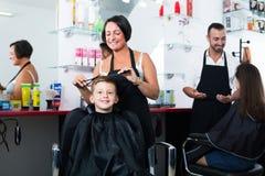 Усмехаясь женский мальчик волос вырезывания парикмахера Стоковая Фотография