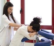 Усмехаясь женский доктор делая массаж Стоковая Фотография RF