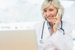 Усмехаясь женский доктор используя компьтер-книжку и телефон Стоковое Изображение