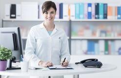 Усмехаясь женский доктор работая на клинике стоковое изображение rf
