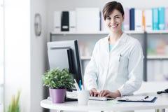 Усмехаясь женский доктор работая на клинике стоковое фото rf