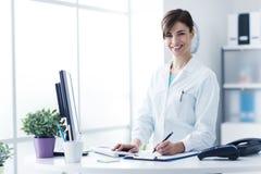 Усмехаясь женский доктор работая на клинике стоковое изображение