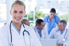Усмехаясь женский доктор смотря камеру пока ее коллеги работают Стоковое Фото