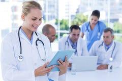 Усмехаясь женский доктор смотря доску сзажимом для бумаги пока ее коллеги работают Стоковые Изображения RF
