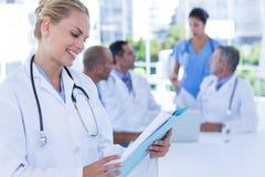 Усмехаясь женский доктор смотря доску сзажимом для бумаги пока ее коллеги работают Стоковое Фото