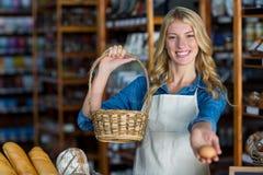 Усмехаясь женский персонал держа корзину и яичко в супермаркете Стоковая Фотография RF