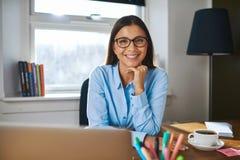 Усмехаясь женский предприниматель на ее столе Стоковая Фотография