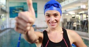 Усмехаясь женский пловец с большими пальцами руки вверх сток-видео