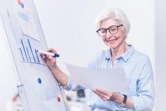 Усмехаясь женский работник делая диаграмму стоковые фотографии rf
