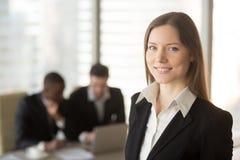 Усмехаясь женский работник офиса представляя в офисе Стоковые Изображения RF