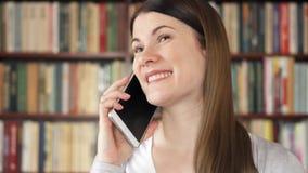 Усмехаясь женский студент колледжа используя мобильный телефон в университетской библиотеке, беседуя gossiping с другом видеоматериал