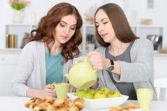 2 усмехаясь женских друз сидя на таблице Стоковая Фотография
