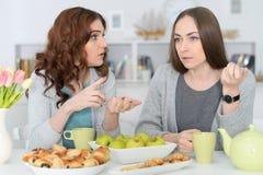 2 усмехаясь женских друз сидя на таблице Стоковое Фото