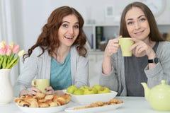 2 усмехаясь женских друз сидя на таблице Стоковые Изображения