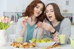 2 усмехаясь женских друз сидя на таблице Стоковое фото RF