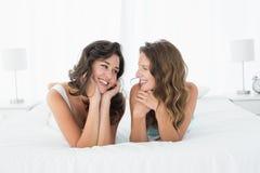 2 усмехаясь женских друз лежа в кровати Стоковое фото RF