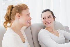 2 усмехаясь женских друз сидя на софе в живущей комнате Стоковое Фото
