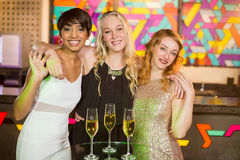 3 усмехаясь женских друз стоя с рукой вокруг в баре Стоковые Изображения