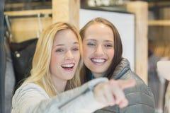 2 усмехаясь женских друз указывая прочь Стоковые Фото