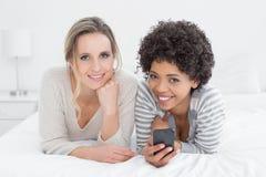 2 усмехаясь женских друз читая текстовое сообщение в кровати Стоковое Изображение RF