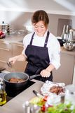 Усмехаясь женское kitchener в форме стоит в кухне на ресторане стоковое изображение